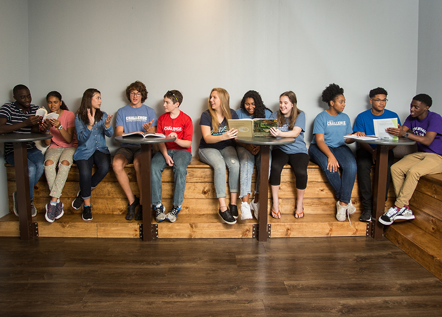 Group of high school homeschool kids reading and talking