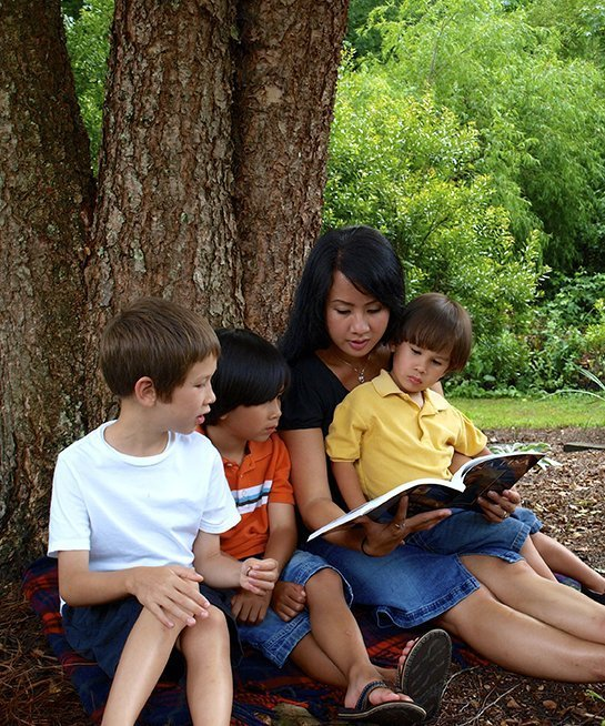 Classical Conversations International homeschool family reading under a tree